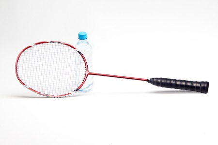 Water bottle behind badminton racket isolated on white background photo