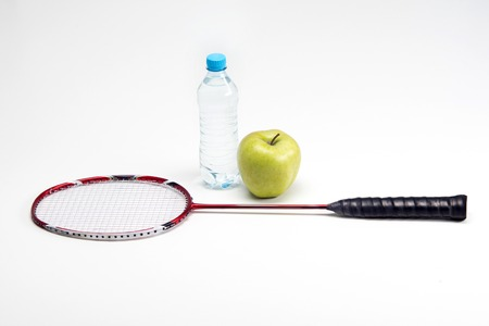 Badminton racket, water bottle and green apple isolated on white background photo