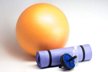 Sports equipment, Fit ball, yoga mat, abs roller and water bottle closeup isolated on white