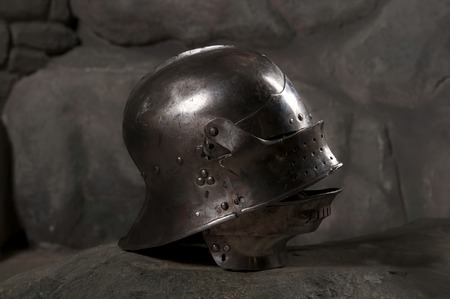 Closeup of knight armor helmet on the dark stone wall background Stock Photo
