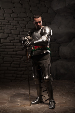 devoted: Medieval Knight posing with sword  and helmet in a dark stone background  Full-length portrait  Stock Photo