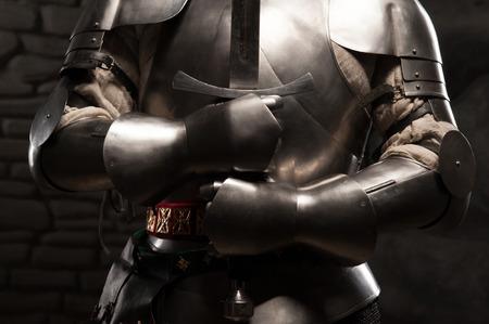Close-up portret van de middeleeuwse ridder in harnas met een zwaard in de donkere stenen muur achtergrond