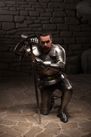 devoted: Medieval knight  kneeling with sword on a dark stone wall background