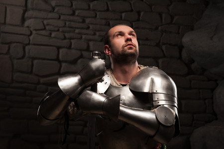 devoted: Closeup portrait of inspired medieval knight looking up and kneeling with sword on a dark stonewall background Stock Photo