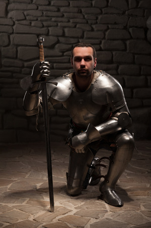 kneel down: Medieval knight  kneeling with sword on a dark stone wall background