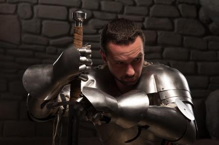 arrodillarse: Primer retrato de caballero medieval mirando hacia abajo y de rodillas con la espada sobre un fondo oscuro muro de piedra
