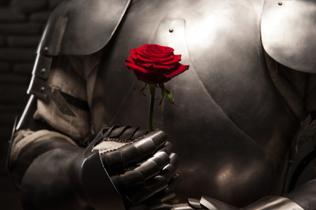 armour: Closeup portrait of medieval knight in armor holding red rose on dark background, romance concept