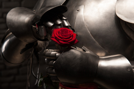 dangerous love: Closeup portrait of medieval knight in armor holding red rose on dark background, romance concept