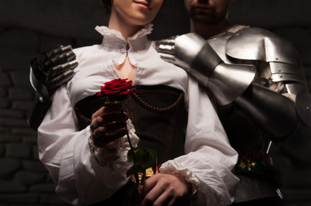 Closeup portrait of red rose, medieval knight embracing beautiful romantic brunette lady from behind, on dark stone background