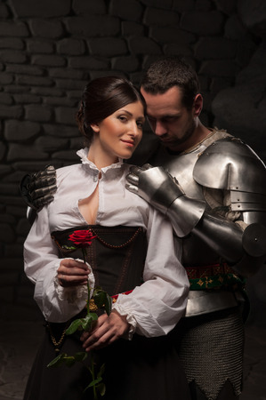 Full length portrait of a couple in historical costumes, medieval knight embracing beautiful brunette lady from behind, on dark stone background
