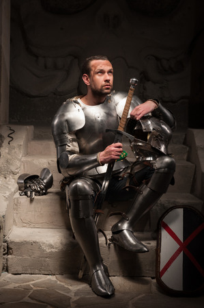 devoted: Portrait of medieval knight in armor with shield and sword sitting on steps of ancient temple with skull, dark background