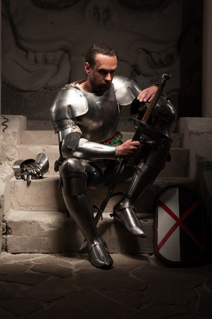 Portrait of medieval knight in armor with shield and sword sitting on steps of ancient temple with skull, dark background