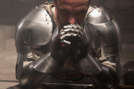 caballero medieval: Retrato de detalle de la armadura del caballero medieval guante que sostiene la espada, fondo oscuro Foto de archivo