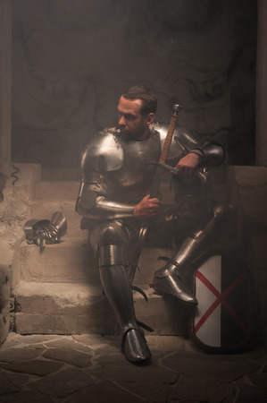 reign: Closeup portrait of medieval knight with helmet and sword sitting on steps of ancient temple in smoke, dark background