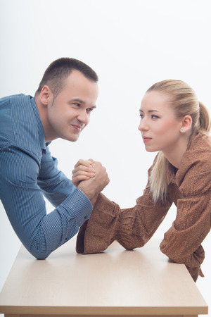 Waistup portrait of a young attractive woman and man fighting on hands isolated on white background photo