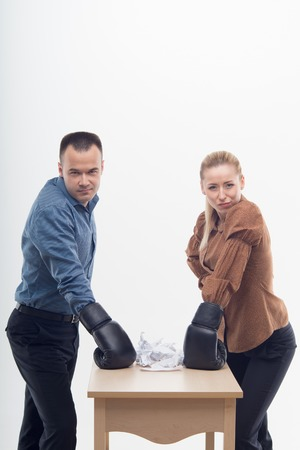 Young attractive business woman and man with boxing gloves are ready for battle, table with paper, isolated on white background Stock Photo