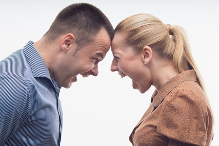 battle of the sexes: Colleagues fighting each other with foreheads together, staring with hostile expressions isolated on white