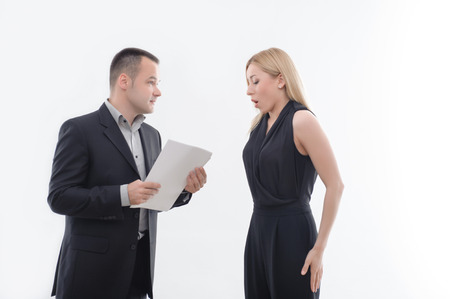 Handsome boss in suit holding blank paper looking precisely at embarrassed young attractive woman employee, isolated on white Фото со стока