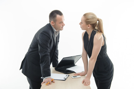 waistup: Waistup portrait of young attractive colleagues discussing something, arguing by the table with laptop and clipboard, isolated on white Stock Photo