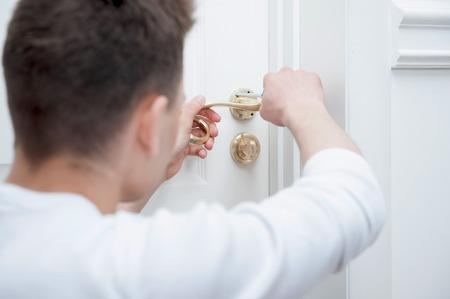 Jonge blanke man vaststelling van de deurklink met een schroevendraaier van achter