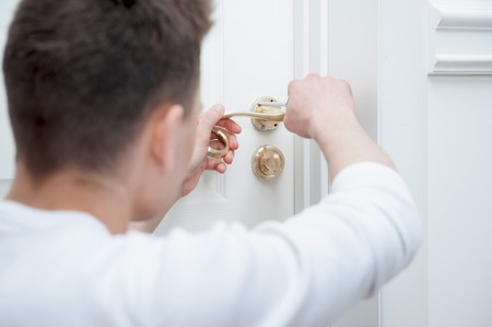 Young Caucasian man fixing the door handle with screwdriver from behind photo