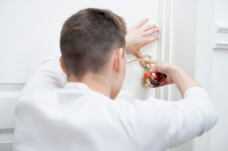 Young Caucasian man fixing the door handle with pliers from behind photo