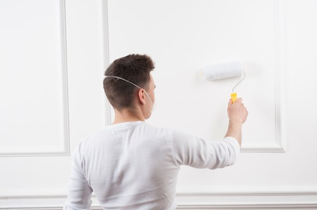House painter, young man wearing safety mask painting with roller by the white wall, view from behind photo