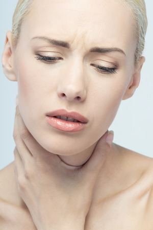 Throat pain concept  Young attractive blonde woman touching her throat isolated on white background photo