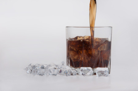 longdrink: Closeup of a tumbler of glowing golden brandy with ice, ice cubes around glass, isolated on a white background