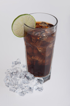 Cola in glass with lemon slice, ice cubes around the glass. Isolated on white background photo