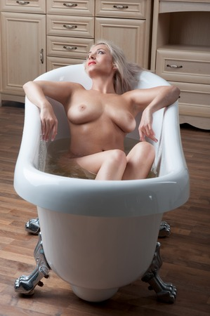 Sexual young blonde nude woman posing with bare breast seductively in the bath Stock Photo