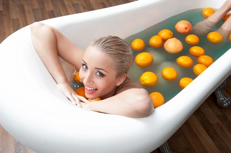 Top view portrait of sexual young blonde nude woman smiling and relaxing in the bath with oranges Stock Photo