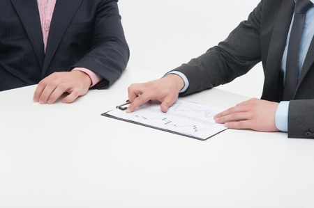 Two business people in elegant suits working in team together with documents, holding clipboard with papers isolated on white background photo