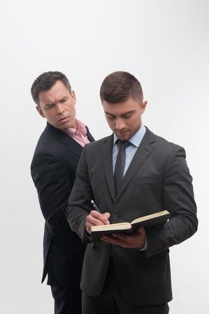 undersign: Senior and junior business people in suits, young handsome employee writing in notebook in front, senior colleague peeping from his back, isolated on white Stock Photo