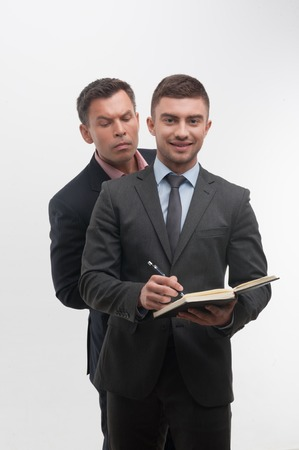 undersign: Senior and junior business people in suits, young handsome employee smiling and writing in notebook in front, senior colleague peeping from his back, isolated on white