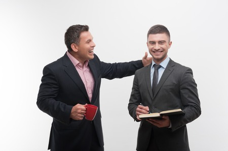 Senior and junior business people discuss something, boss with red cup patting shoulder of young employee, isolated on white background Stock Photo