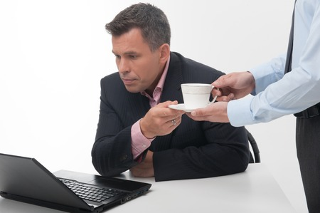 Young handsome office worker assistant brings coffee cup to senior manager sitting at desk with laptop, closeup portrait isolated on white photo