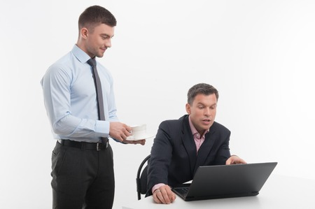 Young handsome office worker holding cup of coffee discusses something with senior manager sitting at desk with laptop isolated on white photo