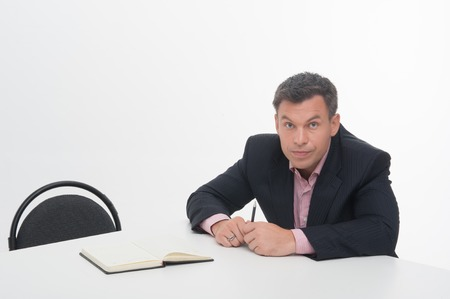 chief executive officers: Senior mature manager sitting at desk, pointing with pen aside, looking at camera isolated on white Stock Photo