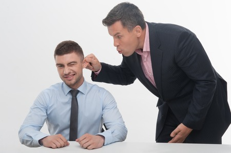 Senior mature manager chief standing by desk pulling his young junior employee ear, isolated on white