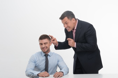 Senior mature manager chief standing by desk pulling his young junior employee ear, isolated on white photo