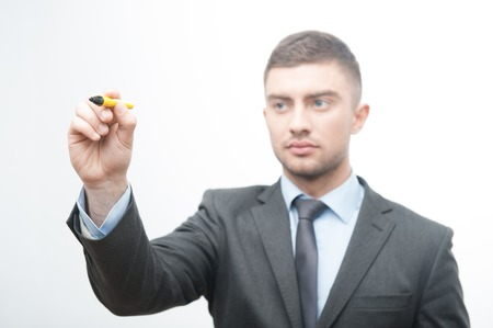 selected: Selected focus portrait of young handsome businessman holding marker and writing, drawing something in the air, isolated on white background