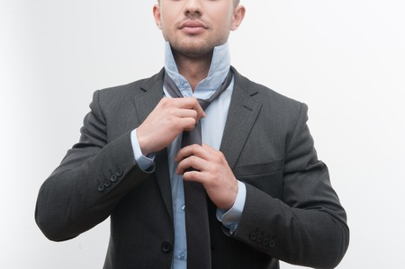 unbutton: Closeup portrait of young smiling handsome businessman in suit putting on necktie isolated on white Stock Photo