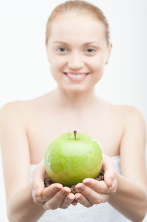 Closeup portrait of young woman in white towel holding coffee beans and green apple, selected focus isolated on white photo