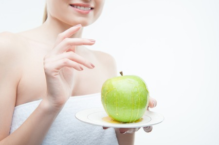 Closeup portrait of young woman in towel holding a plate with green apple covered with honey, isolated on white. Concept of healthy nutrition, beauty and diet photo