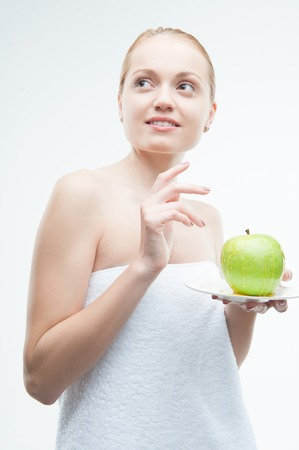 Waistup low angle portrait of young woman in towel holding a plate with green apple covered with honey, isolated on white  Concept of healthy nutrition, beauty and diet photo