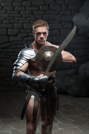 strong toughness: Half length portrait of young attractive warrior gladiator with muscular body posing with shield and sword on dark background  Concept of masculine power, strength