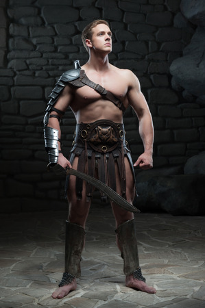 strong toughness: Full length portrait of young attractive warrior gladiator with muscular body posing with sword on dark background  Concept of masculine power, strength