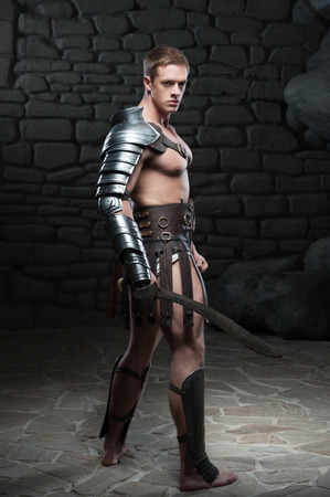 Full length side view portrait of young attractive warrior gladiator with muscular body posing with sword on dark background  Concept of masculine power, strength
