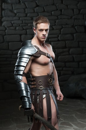 waistup: Waistup vista lateral retrato de joven atractivo guerrero gladiador con cuerpo musculoso posando con la espada sobre fondo oscuro Concepto de poder masculino, la fuerza